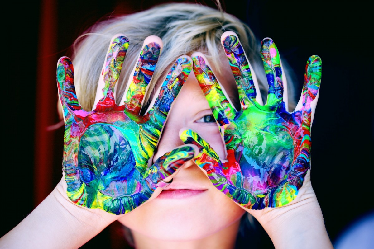 Boy with multi-coloured paint on his hands
