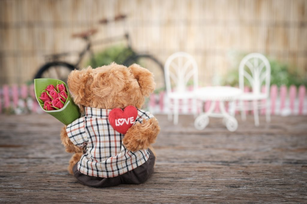 Bear holding red rose