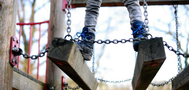 A child balancing on a block bridge